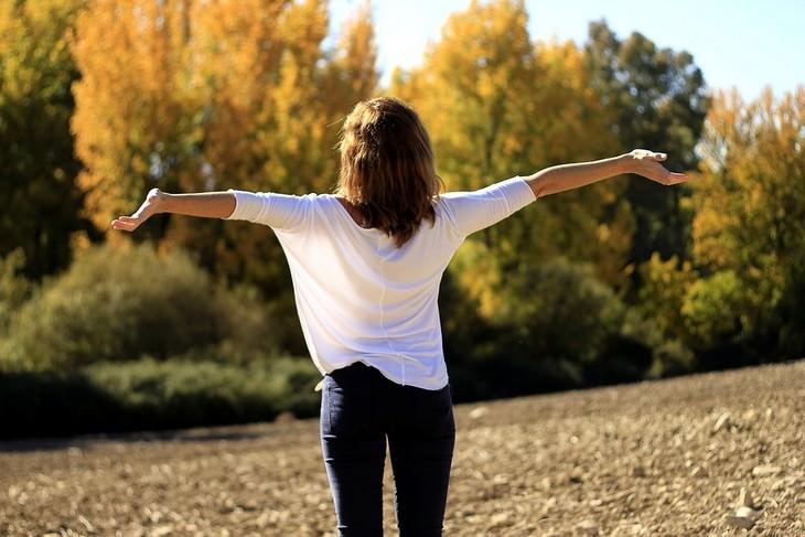 אישה עם זרועות פרושות מעלה עומדת בטבע