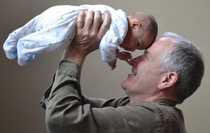 סבא מרים תינוק ומקרב אותו אליו