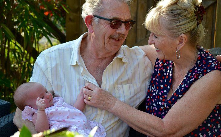 סבא וסבתא מחבקים תינוק