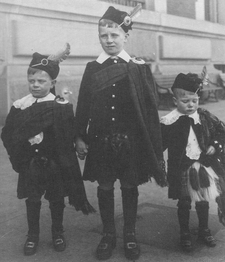 3 ילדים עם כובע ועליו נוצה לובשים חצאית סקוטית מסורתית