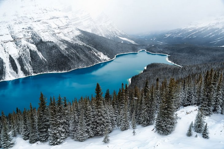 אגם בצבע כחול בוהק מוקף ביער ובהרים מושלגים