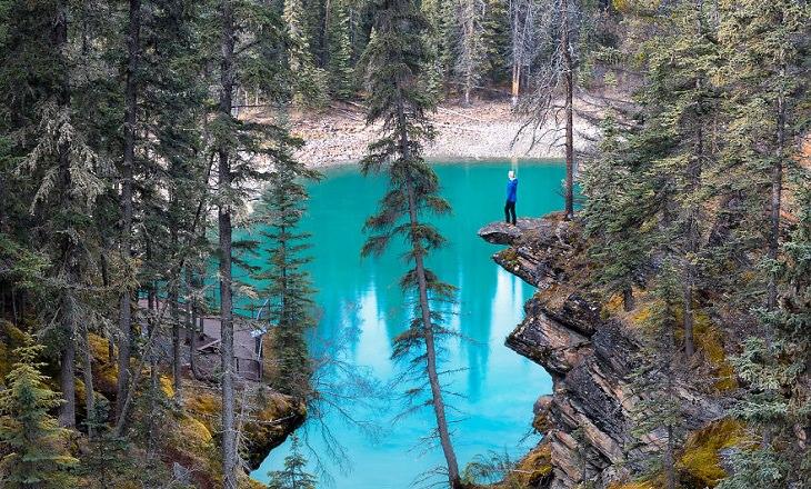 אדם עומד על צוק וצופה אל עבר אגם בצבע טורקיז בוהק