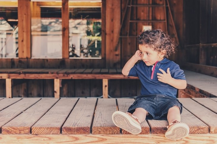 ילד עם אצבע באוזן יושב על רצפת עץ