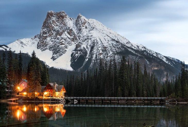 בקתת עץ מול אגם וברקע נשקף הר מושלג
