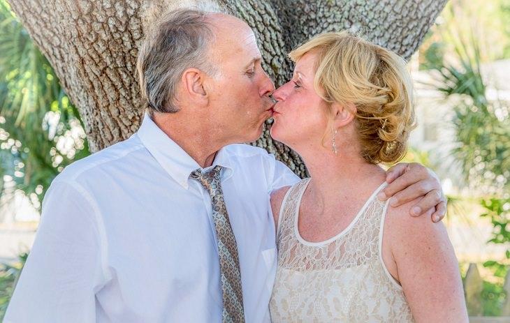 גבר ואישה מתנשקים לצד עץ