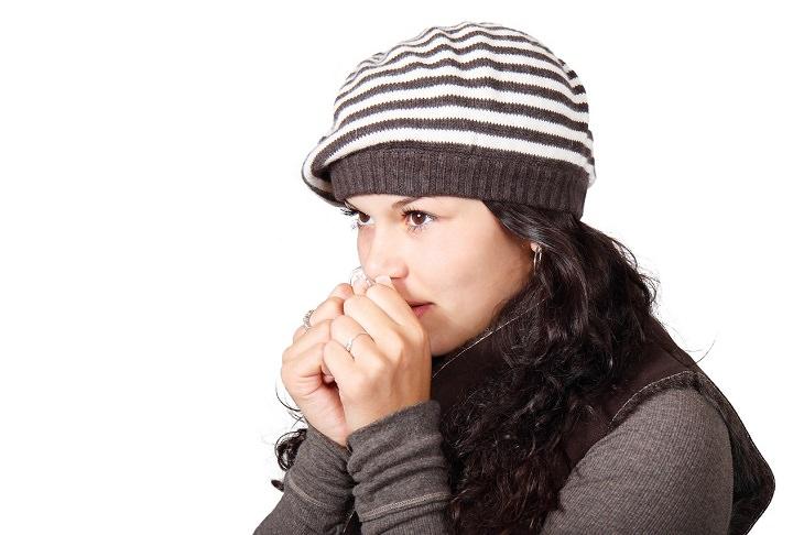 יתרונות בריאותיים של אתרוג: אשה מחככת ידיה על מנת להתחמם