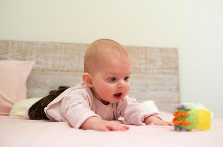כיצד ללמד פעוטות ללכת: תינוק שוכב על הבטן מול צעצוע