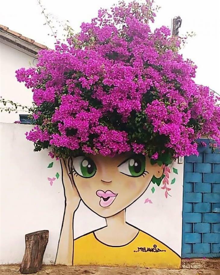 יצירות גרפיטי שמשדרגות את הרחובות: ציור של אישה על חומה, שמעלה יש עץ פרחוני שנראה כמו שיער שלה