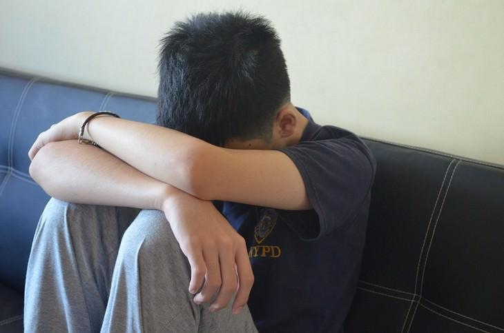 ילד עם ראש מושען על הברכיים שלו