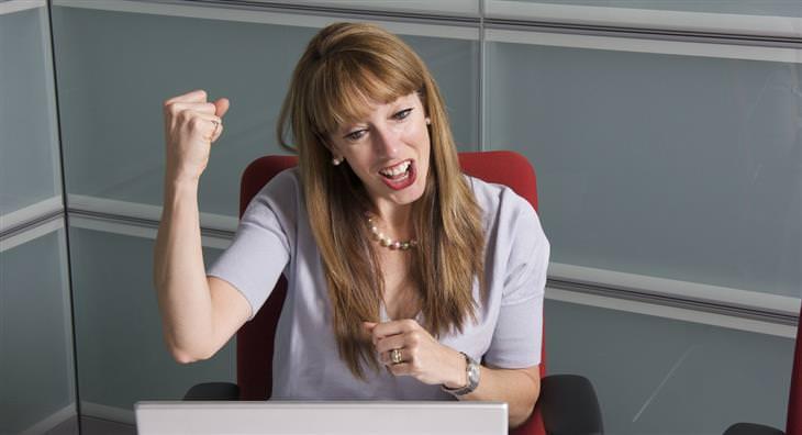 אישה יושבת מול מחשב ומרימה את ידה לאוויר עם תחושת הצלחה