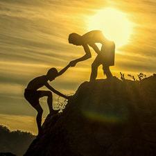 צללית של איש עוזר לחברו לטפס על הר