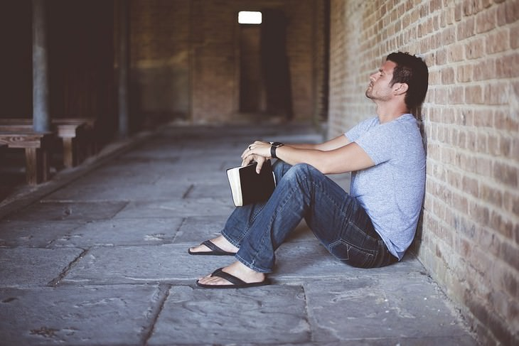 גבר נשען על קיר בישיבה