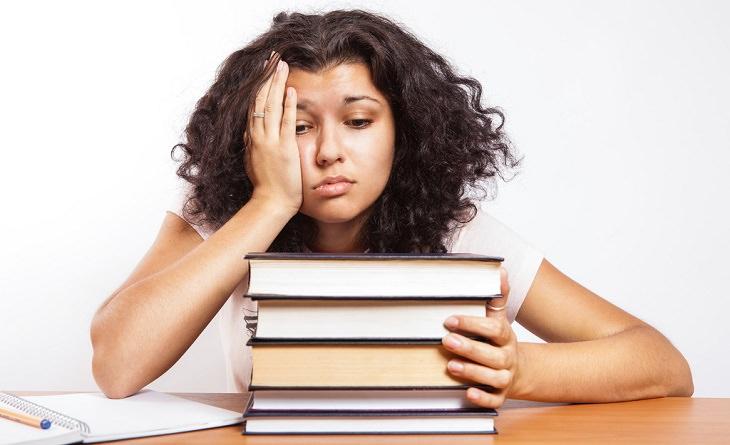 אישה יושבת מול ערימת ספרים ובוהה בהם במבט מיואש