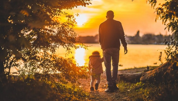 אב וילדו הקטן הולכים לכיוון אגם