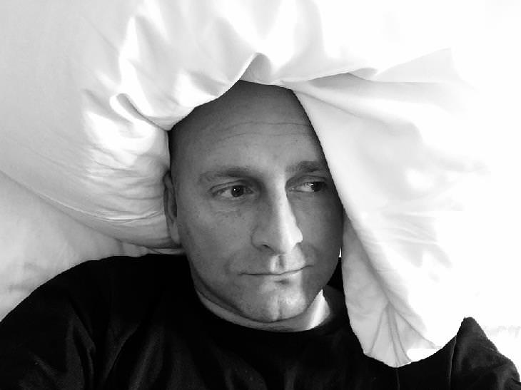 גבר שוכב במיטה עם מבט עגום וכרית סביב ראשו