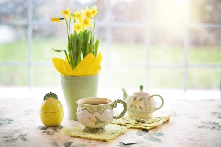אגרטל עם פרחים מונח על שולחן לצד כוס וקנקן תה