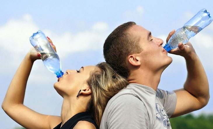 גבר ואישה עומדים גב אל גב ושותים מים