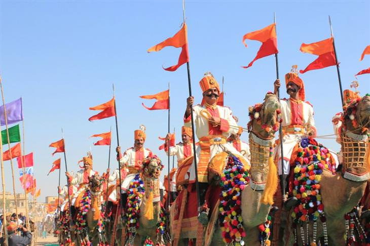 אנשים בלבוש מסורתי ודגלים רוכבים על גמלים