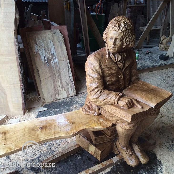 פסל מעץ של אדם יושב וקורא בספר