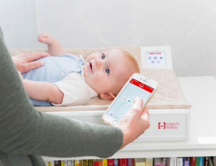 תינוק שוכב על שידת החתלה חכמה ואבא מחזיק סמארטפון בידו עם האפליקציה של השידה החכמה