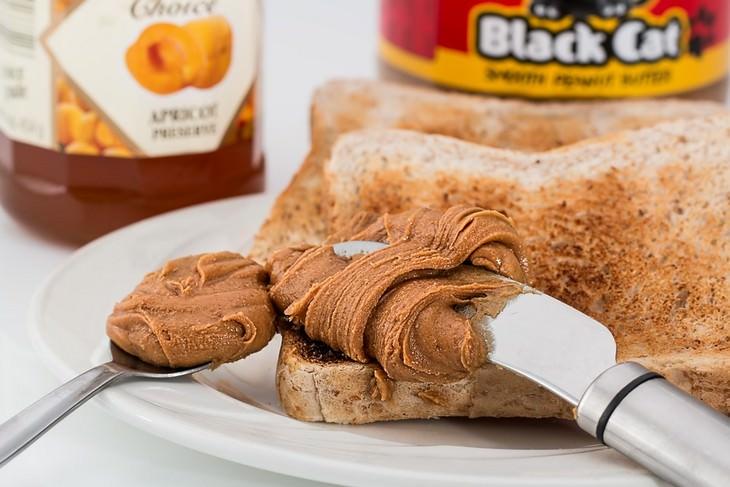 צנים על צלחת עם סכין שמורחת עליו חמאת בוטנים וכפית עם חמאת בוטנים לצידה