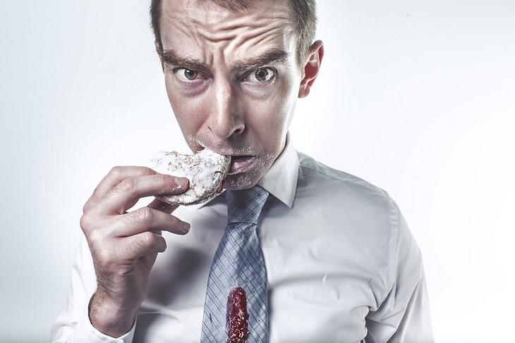 אדם אוכל עוגיה עם כתם ריבה על העניבה