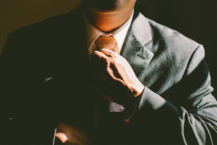 גבר בחליפה מהדק עניבה לצווארו