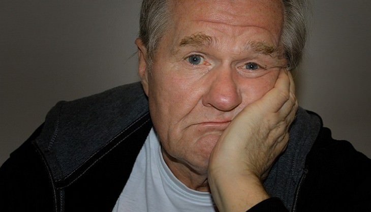 איש מבוגר מניח את ראשו על היד