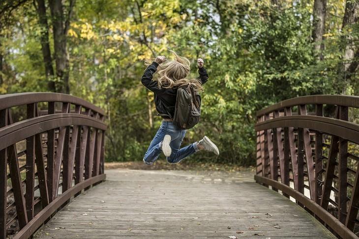 אישה עם תיק גב קופצת על גשר