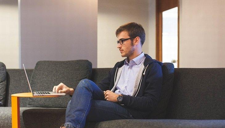 גבר יושב על ספה מול מחשב נייד