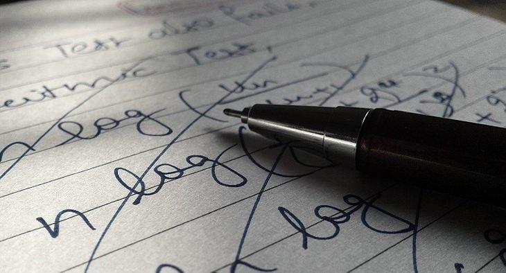 עט ודף שעליו כתובות מילים מחוקות