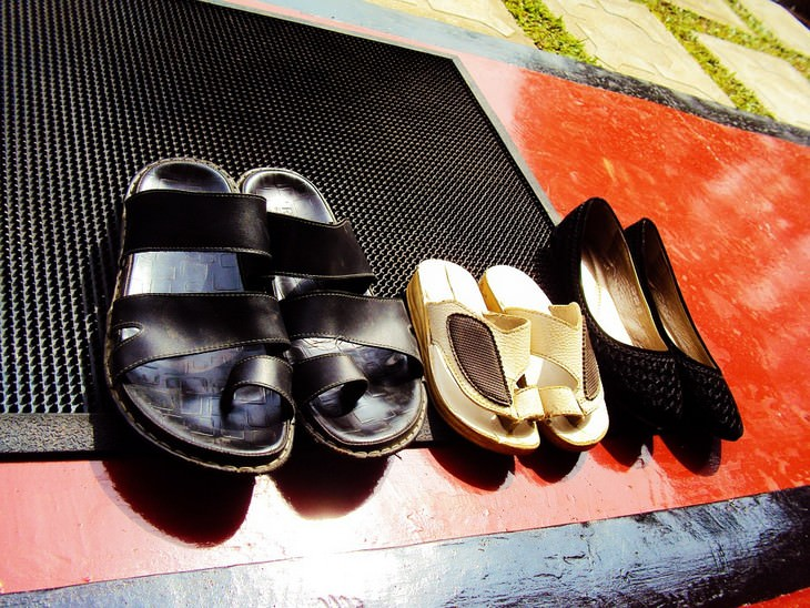 שלושה זוגות נעליים מונחות מחוץ לדלת כניסה