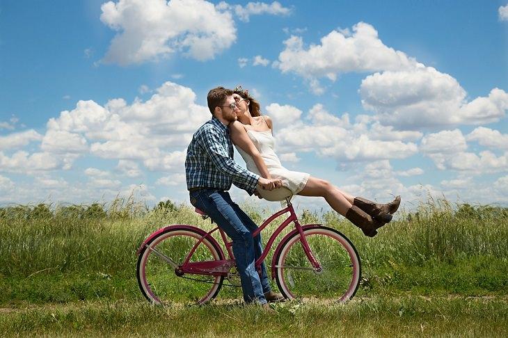גבר ואישה נוסעים על אופניים בשדה ירוק, כשהאישה מנשקת את הגבר