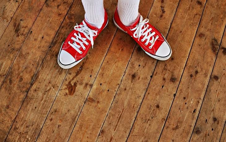 צילום של כפות רגליים עם נעלי ספורט על רצפת עץ