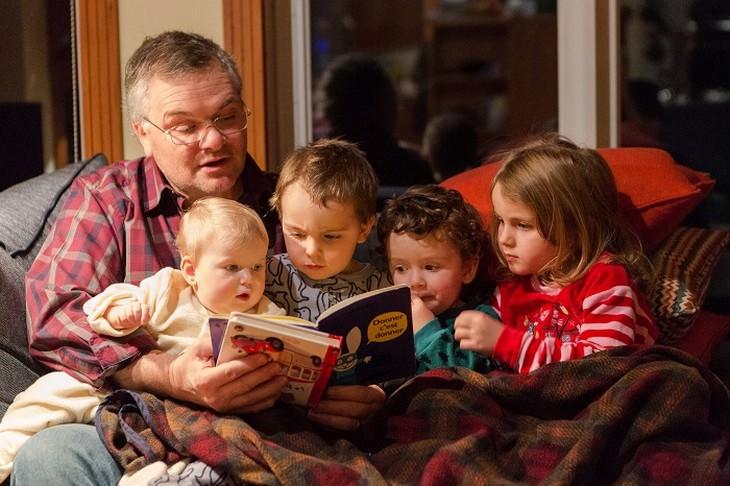 אבא קורא ספר עם 4 ילדים