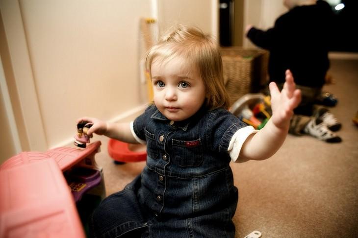 ילדה קטנה משחקת בבית בובות