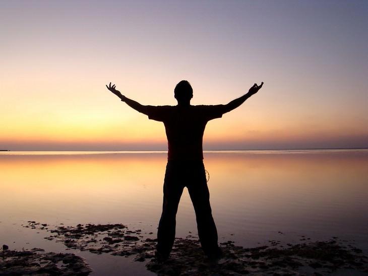 אדם מרים את ידיו מעלה מול שקיעה בים