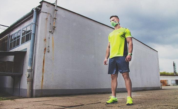 אדם בלבוש ספורטיבי עוטה מסיכה על פיו ואפו