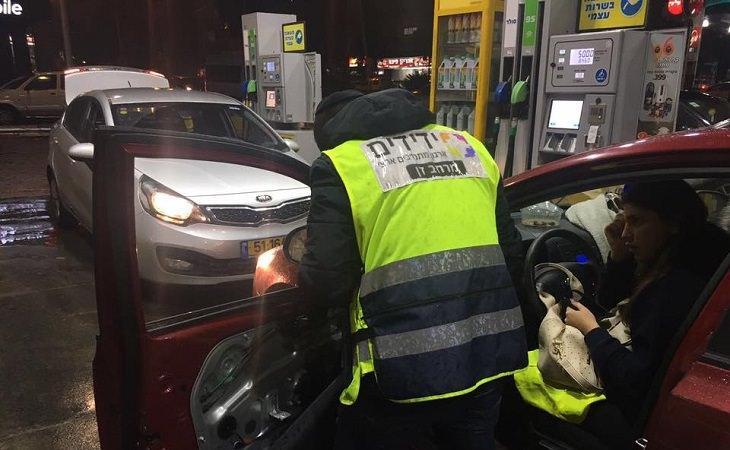 מתנדב מסייע לאישה ברכב