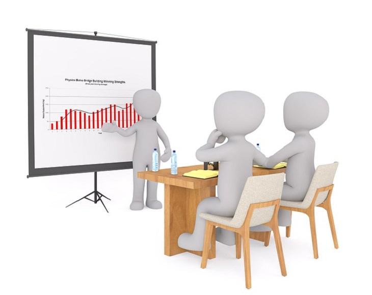 איור של שני אנשים יושבים מול אדם שלישי שמסביר להם גרפים