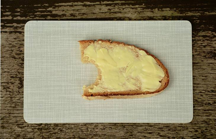 חמאה מרוחה על פרוסת לחם