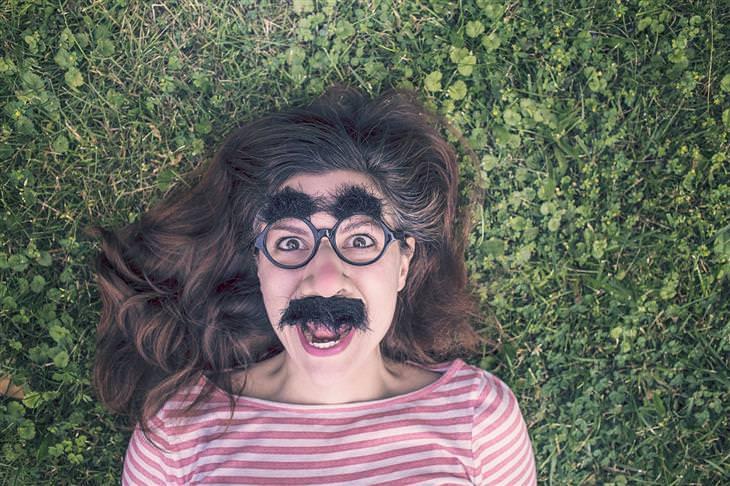 אישה שוכבת על דשא ומחייכת, ועל פניה משקפיים ושפם