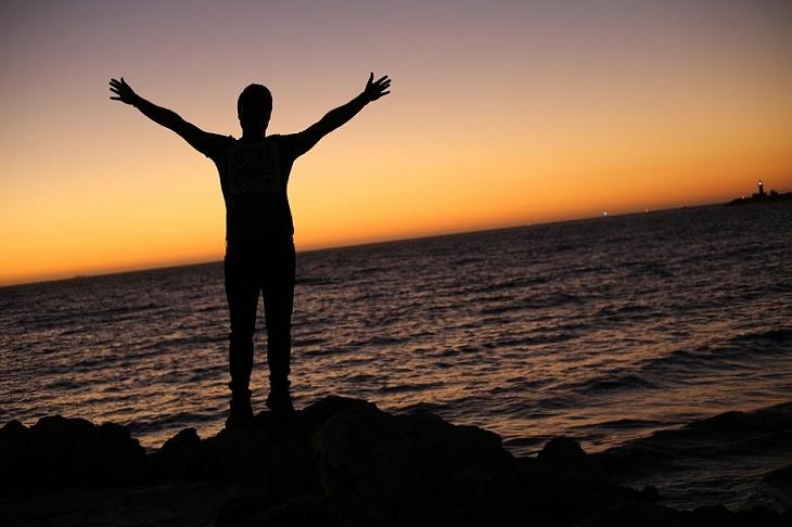 צללית של איש פורס ידיים, על חוף הים, מול צבעי שקיעה