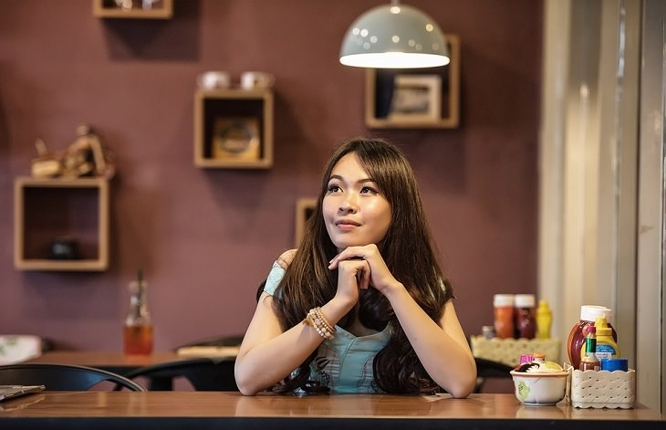 אישה יושבת ליד שולחן ומביטה לאופק