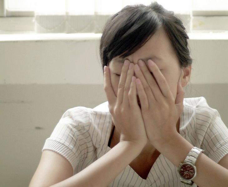 אשה מכסה את עיניה בידיה