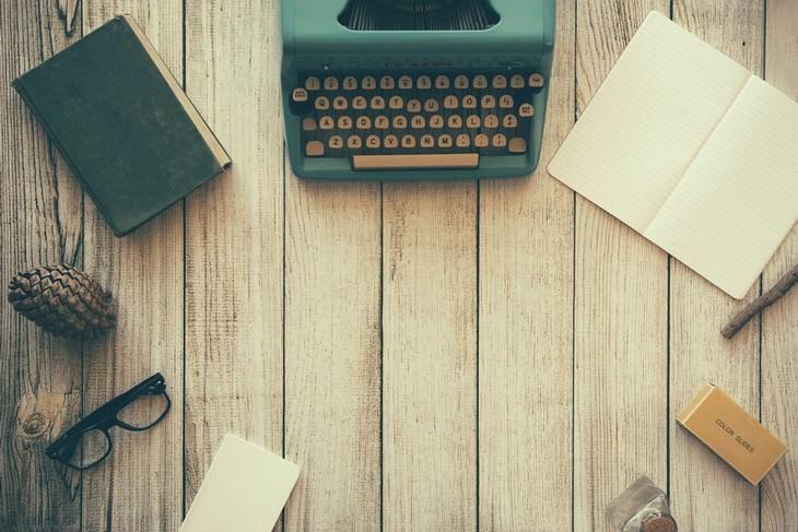 שולחן עם מכונת כתיבה, דפים ועטים