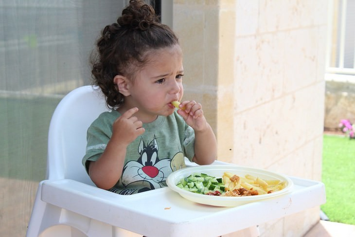 פעוט בכיסא ילדים אוכל צ'יפס מהצלחת