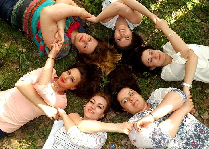 נשים מחוייכות שוכבות על דשא ואוחזות ידיים