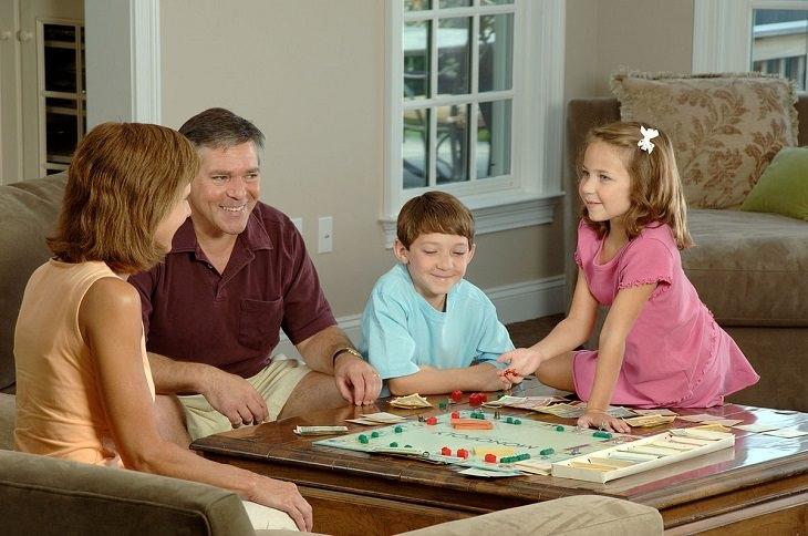 משפחה משחקת משחק לוח סביב השולחן בסלון