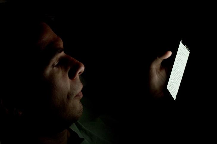 אדם קורא בסמארטפון שלו בחושך